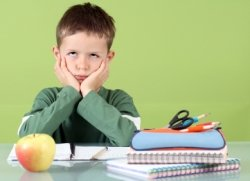Bored Elementary School Boy Writing Assignment